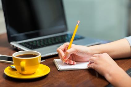 business, education, people, technology and lifestyle concept - close up of woman writing to notebook with pencil